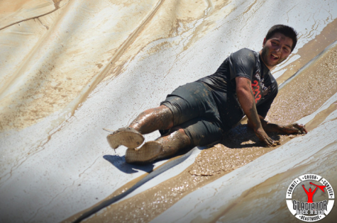 Argeen Ghazarian sliding down one of the mud run obstacles into a pit of mud.