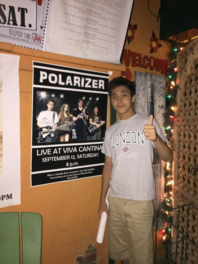 Tristan O'donnell posing next to the band's poster.