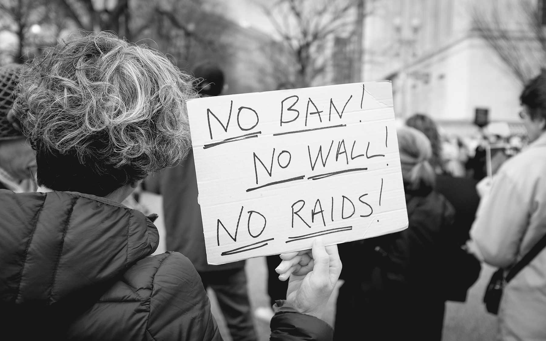 A protester holding a sign against Trump's executive order.