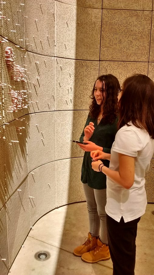 Sophomores Madalynn Carr and Christine Chang observe a wall with 1.2 million holes, representing the number of children killed in the Holocaust. Inside some of the holes are paper cutouts visitors can take from a box and insert into the holes. The cutouts feature the photos and names of children who perished. Visitors can write little prayers or reflections on them.