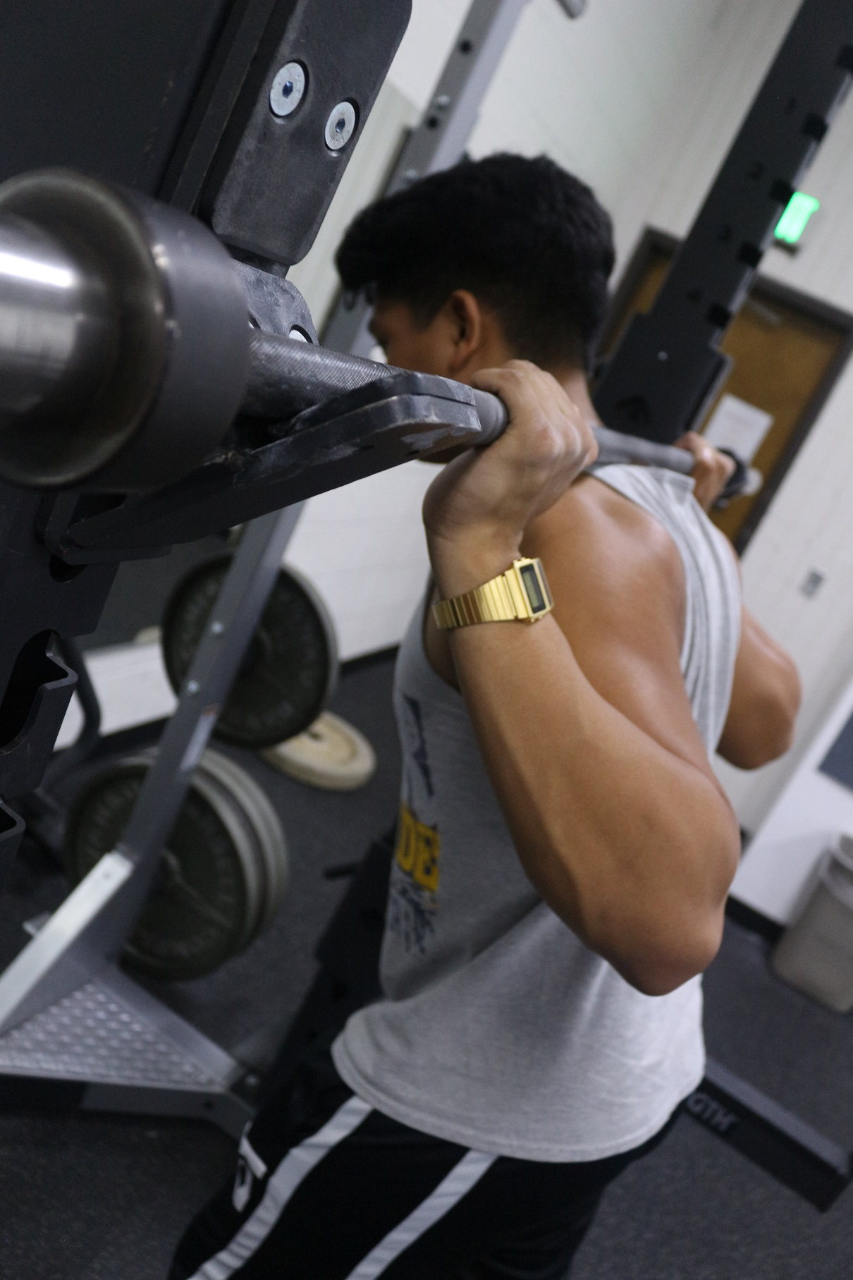 Senior James Tumbucon sets up for warmup squats with an empty barbell at the Glendale YMCA.
