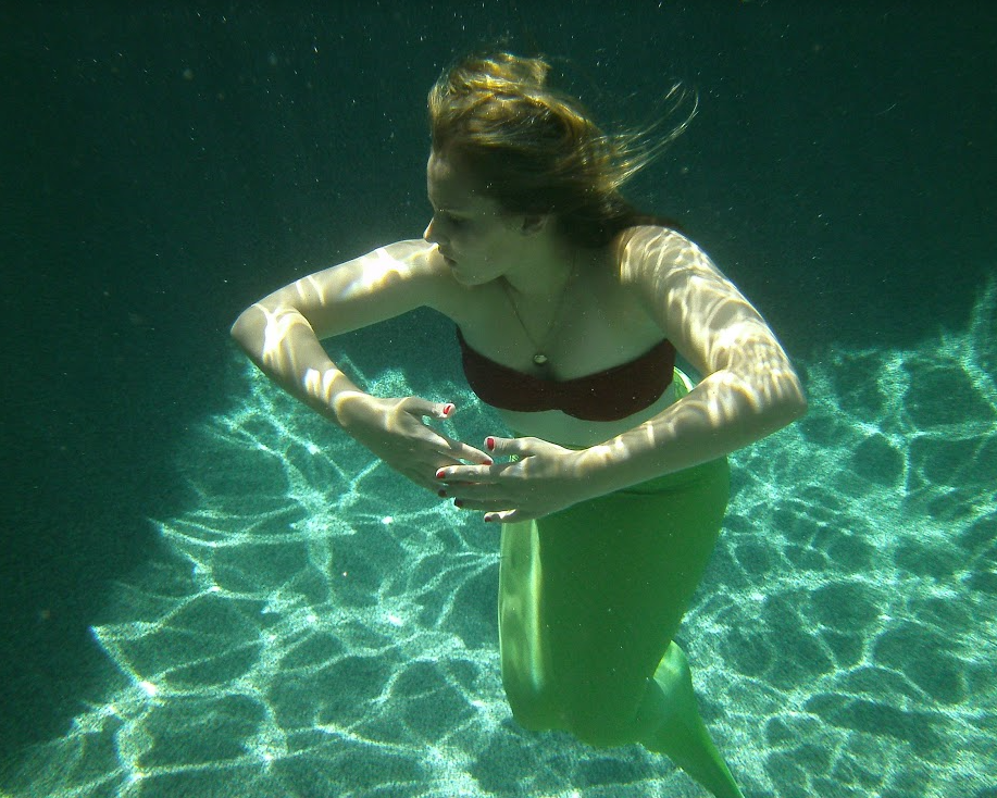 Junior Anna Herrin poses for a picture underwater.