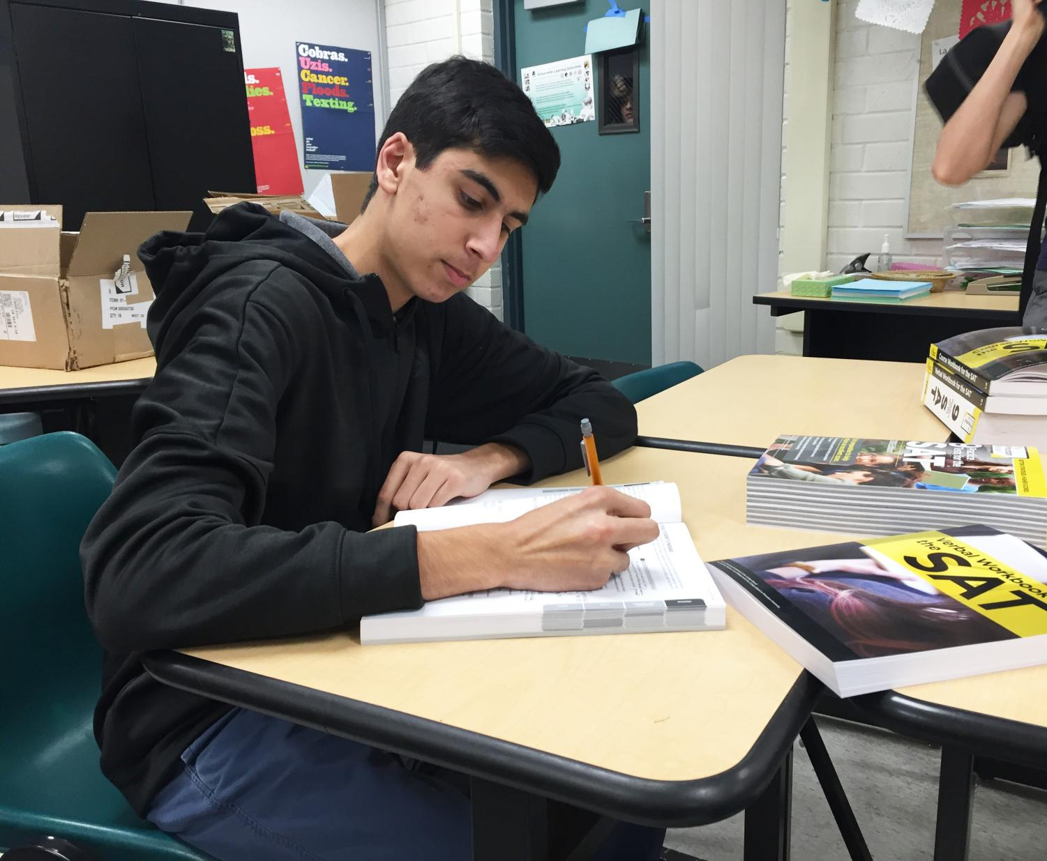 Junior Abdullah Hasan completes practice problems in his SAT workbook, provided for free by The Princeton Review.