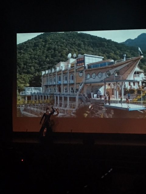 Clark student performing a beautiful dance with photos of  Artsakh in the background.