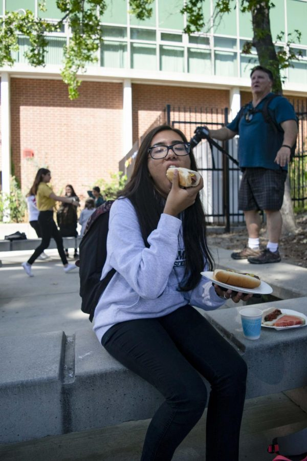 Senior Sangam Sharma grabs a freshly grilled hot dog from Mr. Pruitt at the senior barbecue.