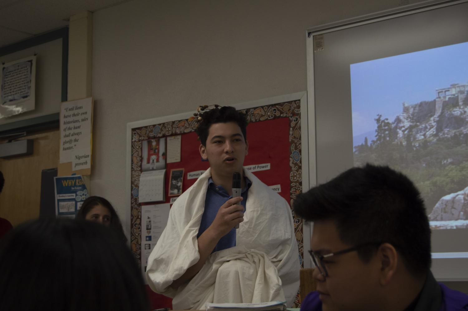 Student Iain Mendez role plays as an ancient Greek civilian during a discussion.