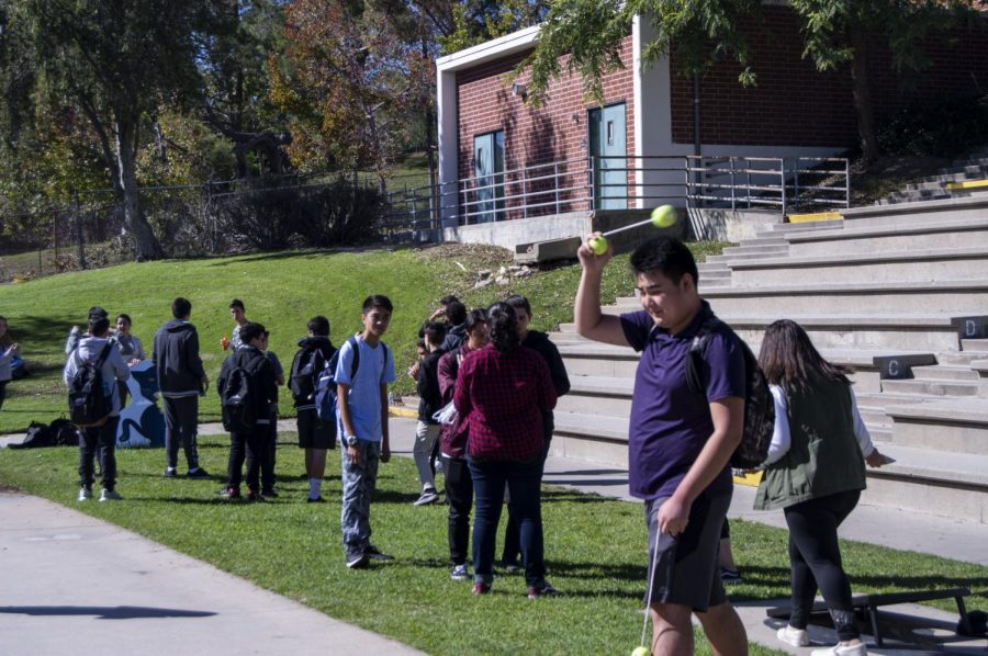 Students play the ball toss game during Clarktoberfest at a club's booth in the amphitheatre.