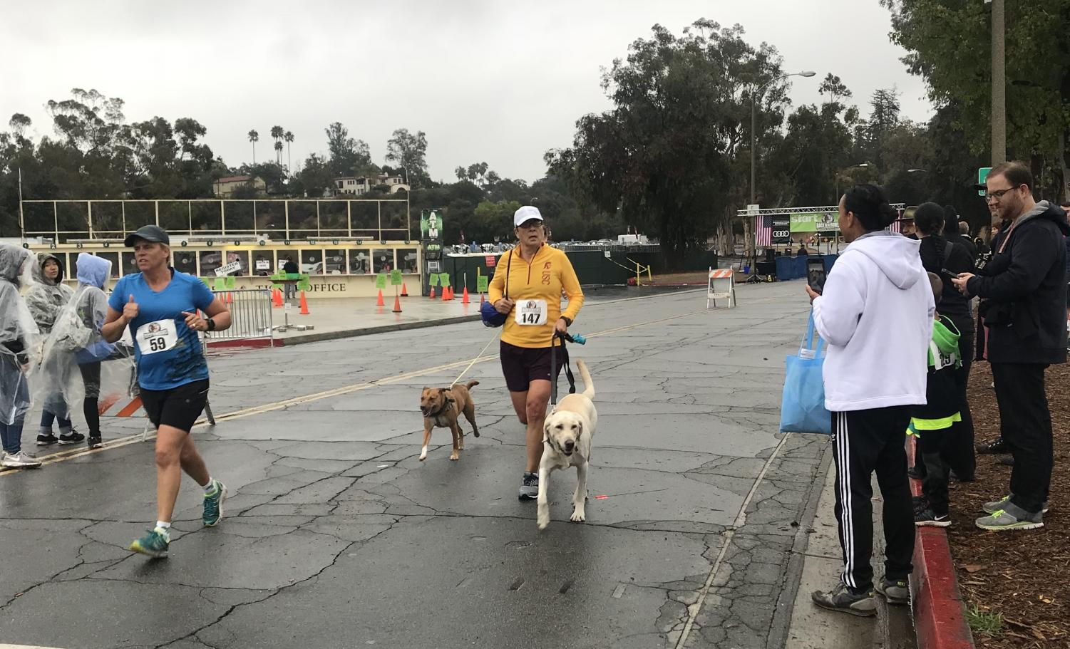 Runner Amy Parker finishing the race with her two dogs.