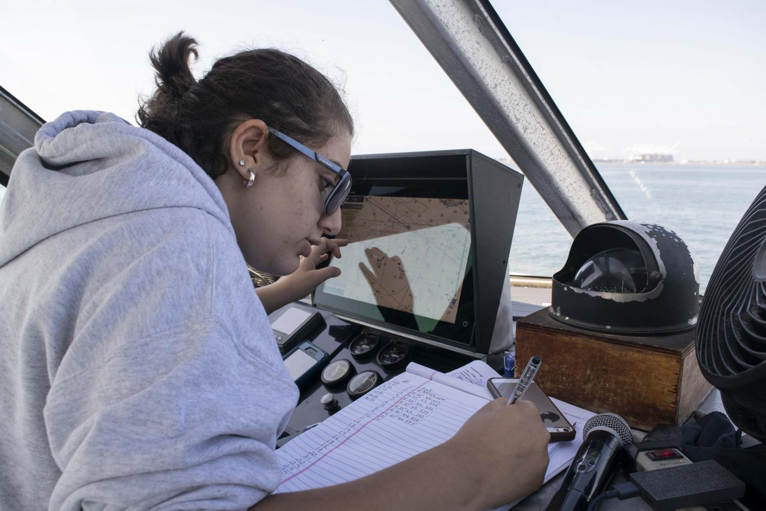 Senior Shelia Mgrtichian records coordinates after the van veen grab was deployed.