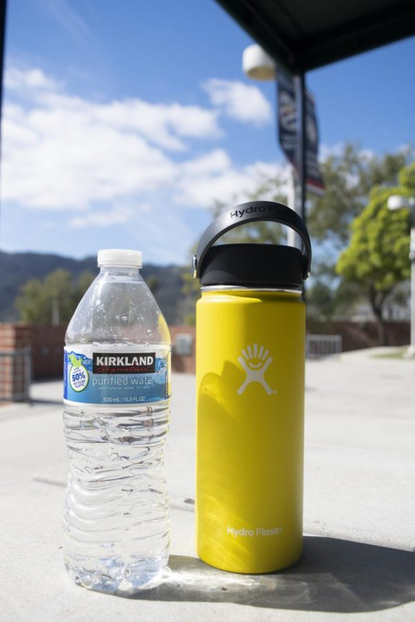 An+18-oz+yellow+wide+mouth+Hydro+Flask+and+a+Kirkland+Signature+plastic+bottle.++