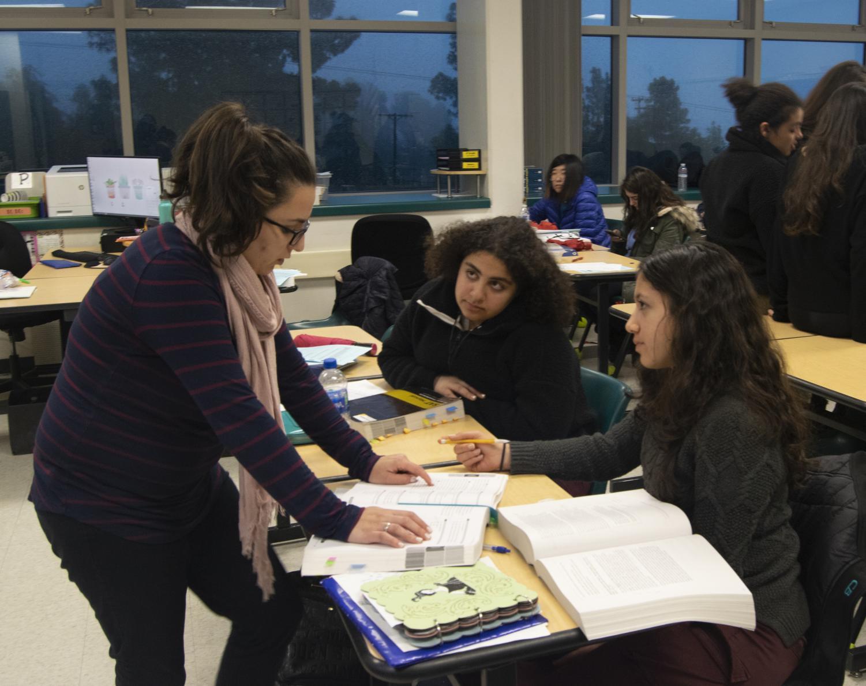 English teacher, Narine Tatevosian, assists juniors Ella Ramamurthy and Aline Zargarian on a writing problem during the SAT class.