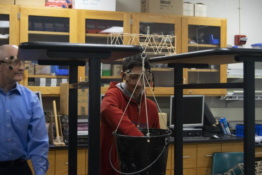Freshman Greg Djalayan inserts a weight into the bucket to test the strength of his bridge.