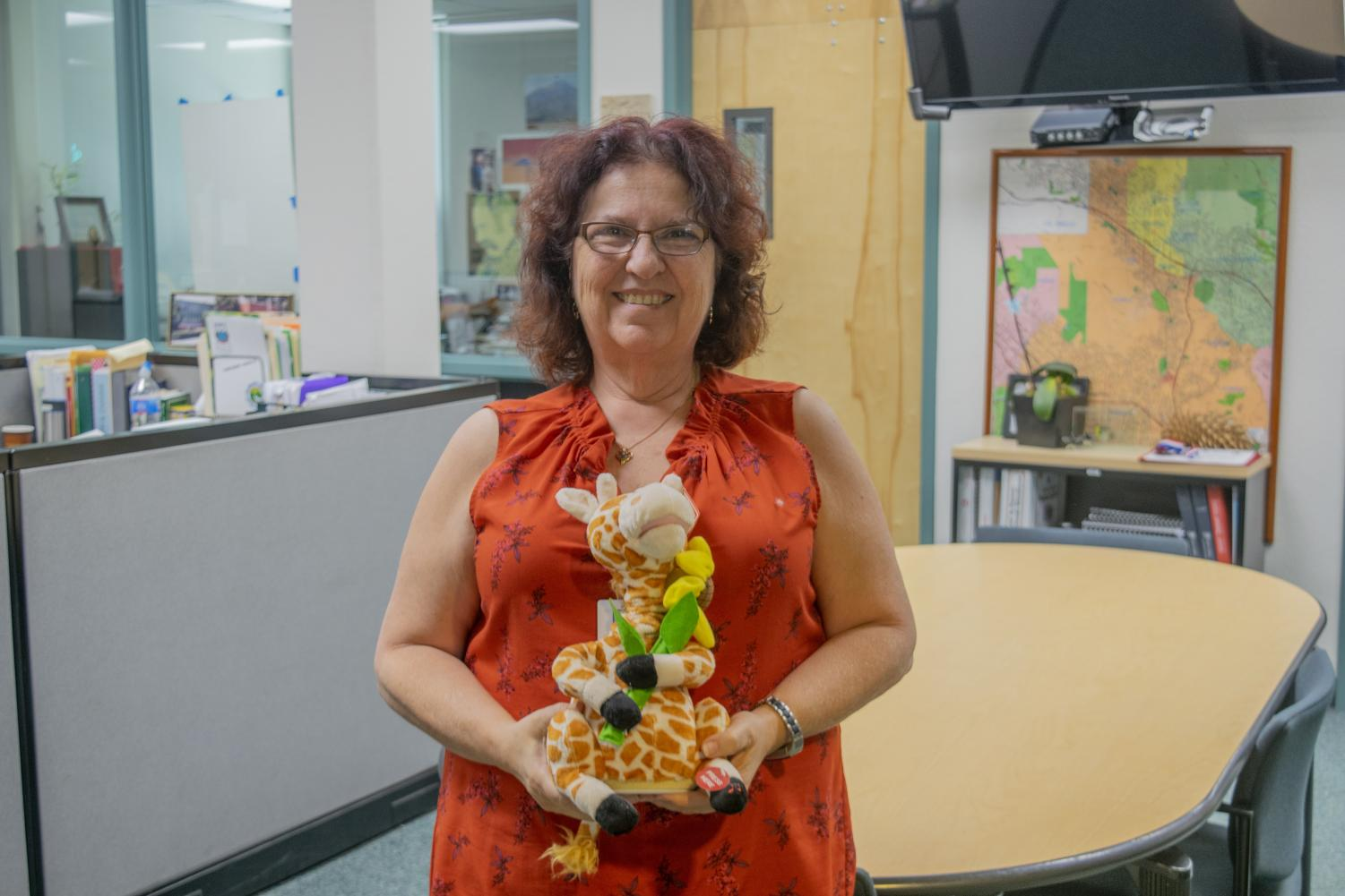 Ms. Howe, one of Clark's counselors, holding one of her iconic giraffes.