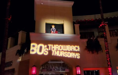 Chucky from the 1988 movie Child's Play peers out over a ledge during Universal's '80s throwback-themed horror night and entertains three intrigued guests.