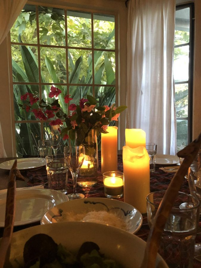 The table is set with candles and a bowl full of Parmesan cheese, ready for the dinner party on Friday night.