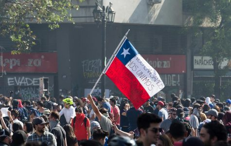 """Protesters storm the streets of Santiago. The flag has written on it """"we got tired. We united so that never again in Chile will sister blood be spilled. No more violence."""""""