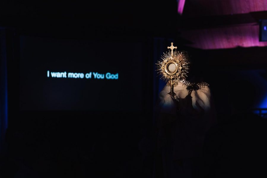 During+Adoration%2C+Father+Jim+of+Holy+Family+Church+held+up+the+Eucharist+as+the+LIFE+TEEN+band+sang+%22Set+a+Fire.%22