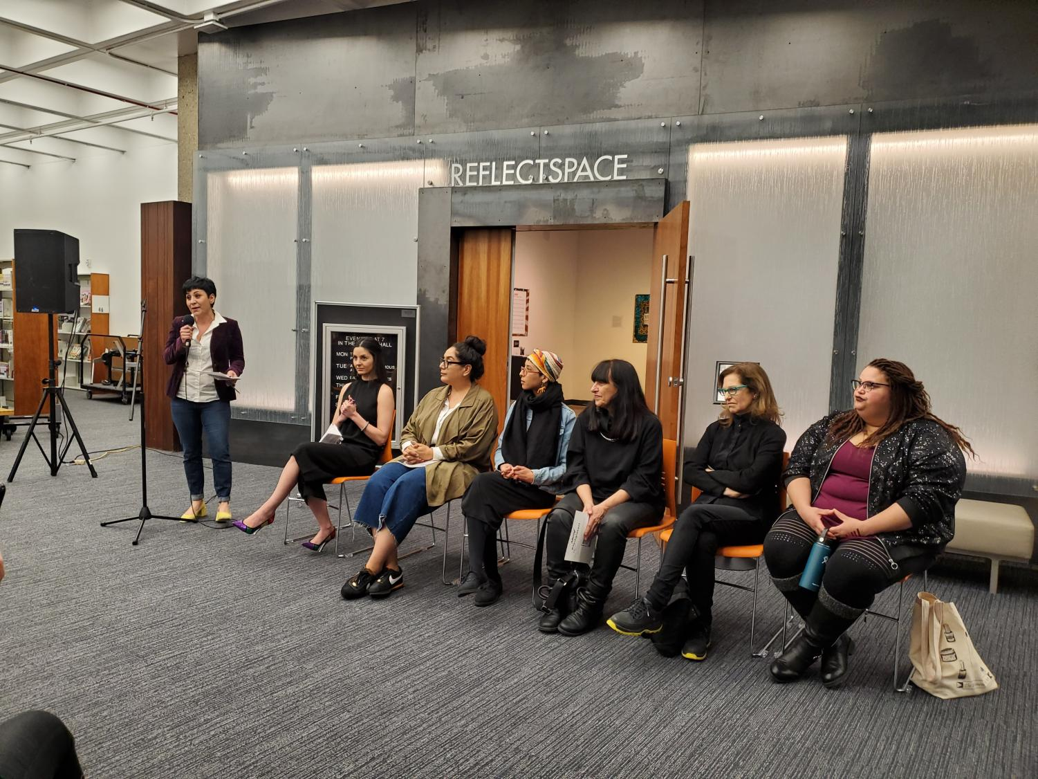 Anahid Oshagan introduces seated artists April Bey, Erika Rothenberg, Joey Forsyte, Jess Castillo, and Lucia Torres (from right to left) with co-curator Ani Ohanessian seated beside her.
