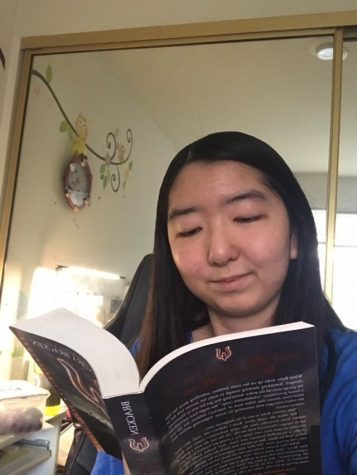 Lauren Chang reading The Darkest Minds by Alexandra Bracken.